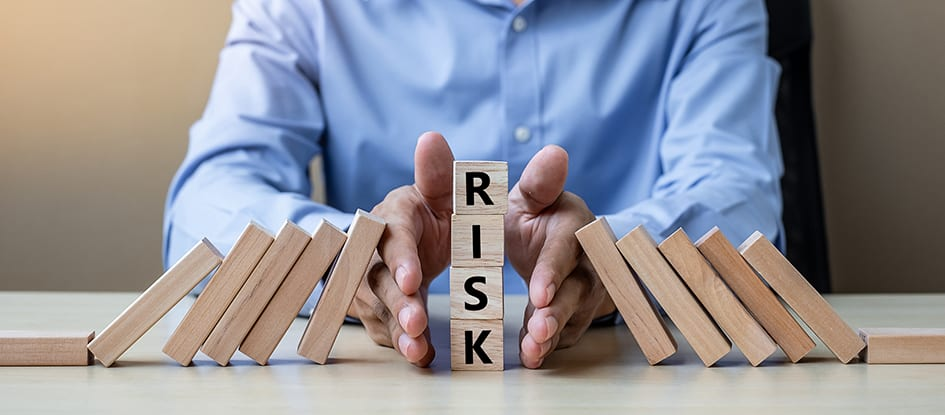 Risk Management - Businessman hand Stopping Falling wooden Blocks or Dominoes.